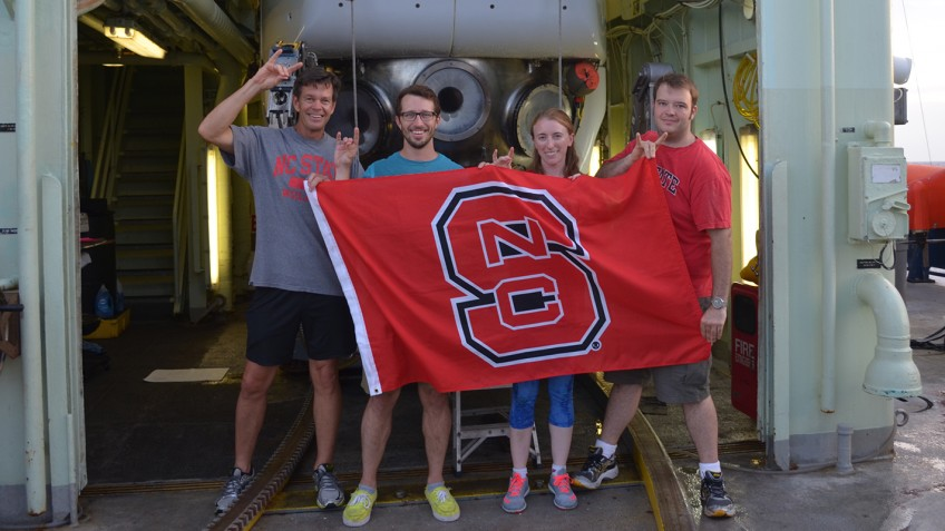grop holding NC State banner
