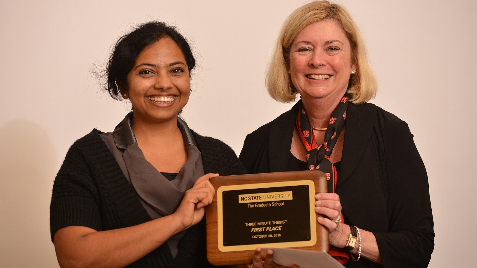 Haritha and Dean Grasso hold award plaque
