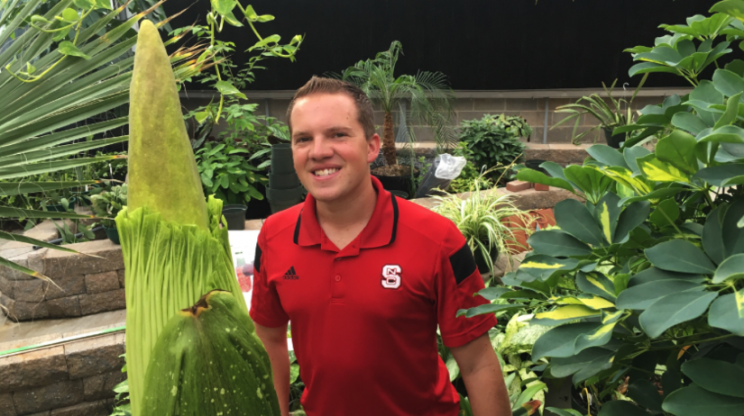 Graduate student Brandon Huber and the corpse flower.