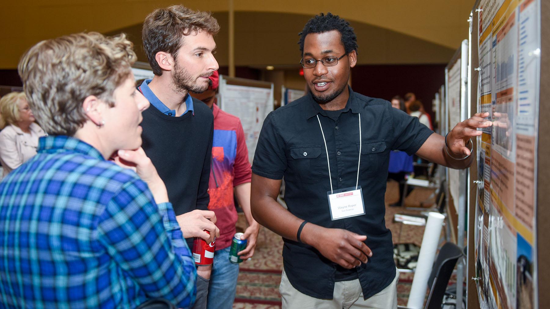 students sharing posters at symposium