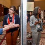 students sharing posters at symposium