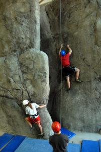 students climbing rock wall