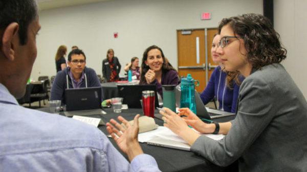 Students and postdocs discuss job documents.