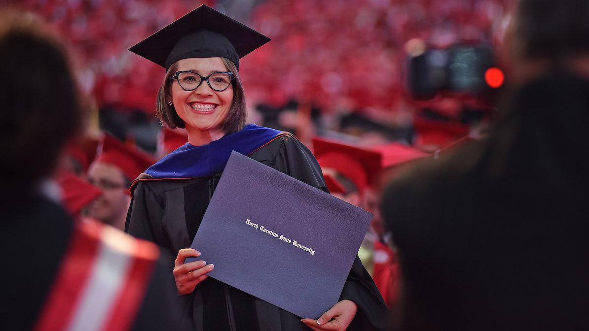 PhD graduate holds diploma