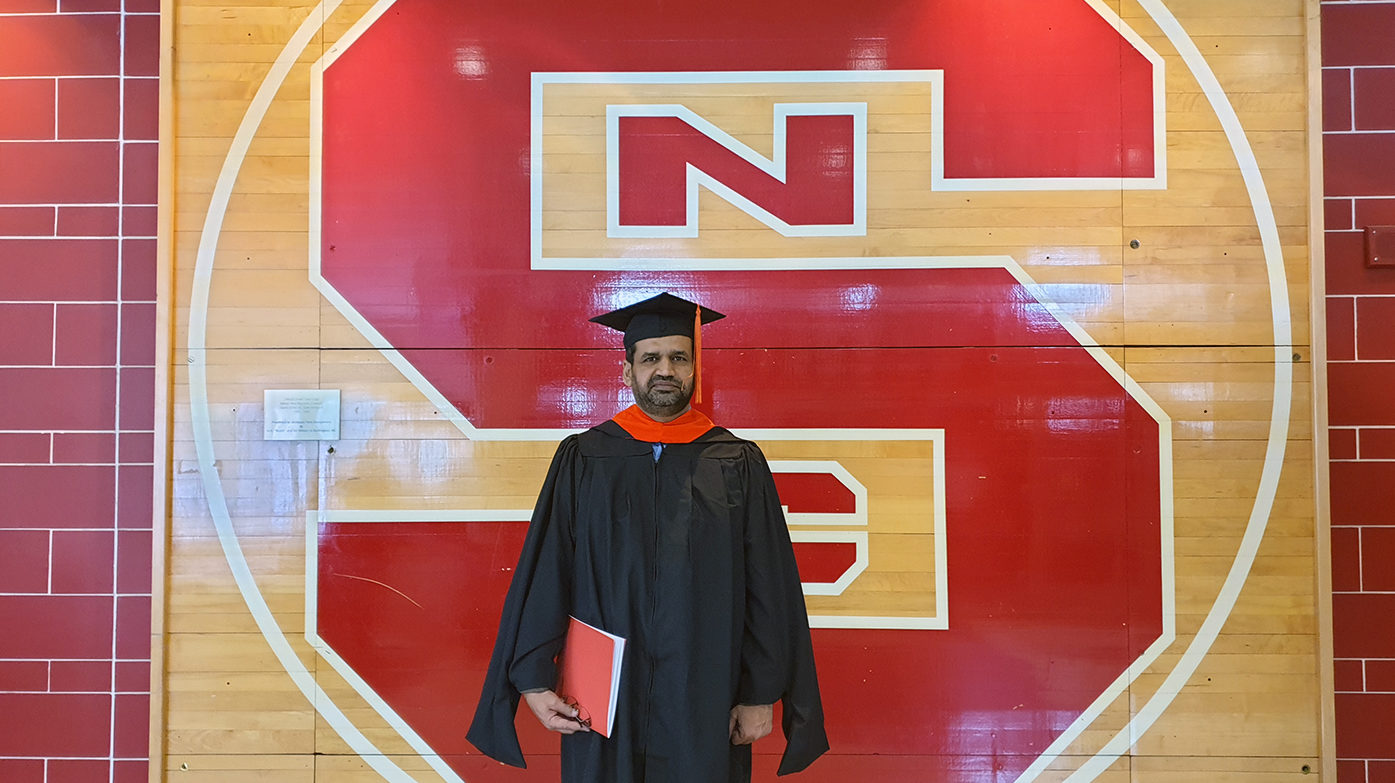 Israr Ul Haq, an Engineering Online student, poses near NC State's logo on campus.
