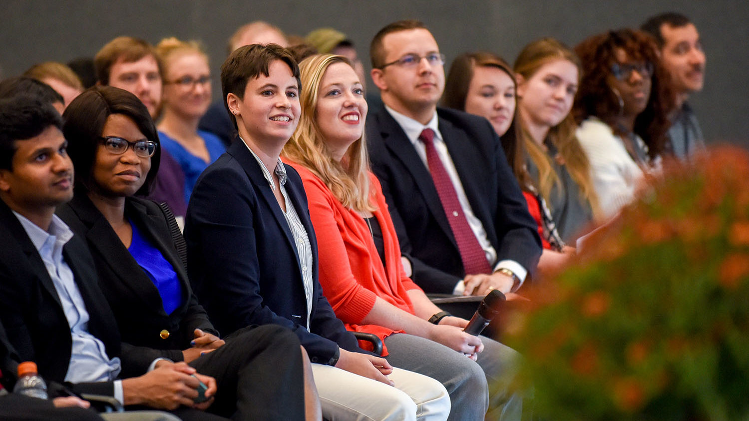 Three minute thesis finalists seated watching another 3 minute thesis presentation.