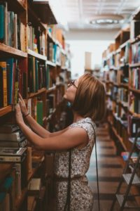 Woman surveying books in a library