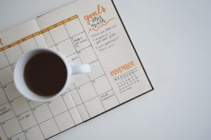 Coffee on top of a planner that has specific goals for the month written