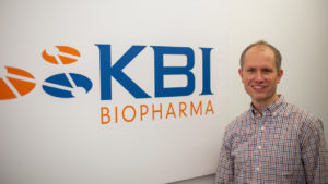 Dane Grismer with the KBI Biopharma logo on a wall