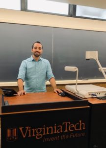 """Tim Beck stands at the front of his classroom with the words """"Virginia Tech: Invent the Future"""" printed on the front of his desk"""