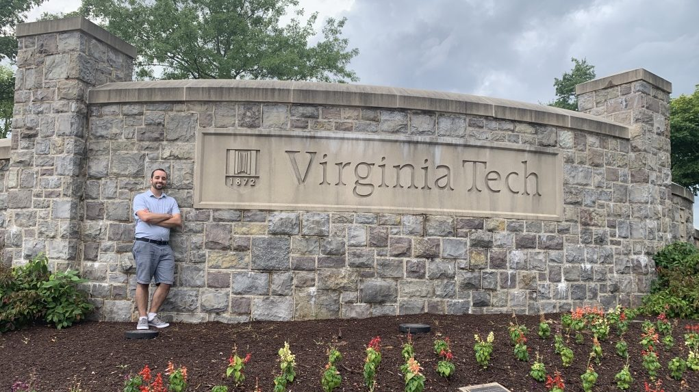 Tim Beck leaning against the Virginia Tech University stone welcome sign