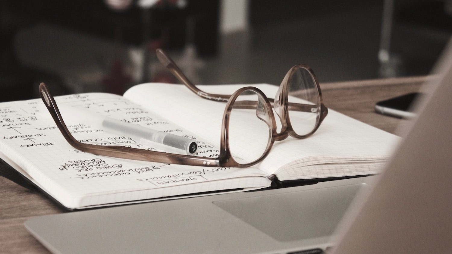 a pair of glasses resting on a journal with writing in it which is obscured