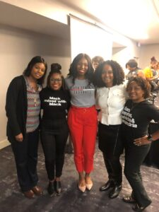 Women of color group standing together at a conference, smiling at the camera