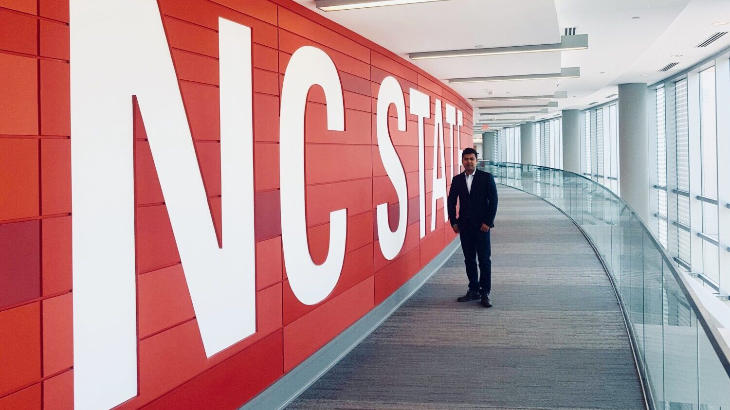Manik Chandra Biswas standing in front of large NC State sign